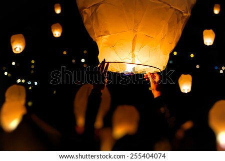 Make A Wish.Yellow lantern in human hands on dark background  - stock photo