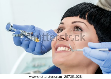 Make happy client the anesthesia. Dentist makes the process of treatment of a beautiful young girl. - stock photo