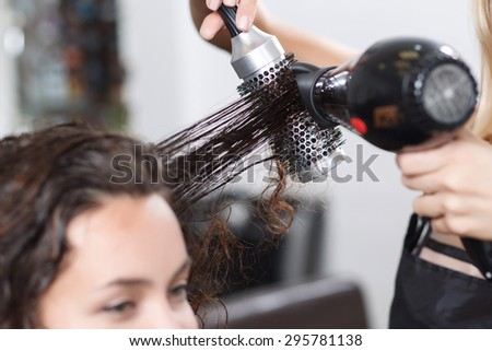 Make it dry. Selective focus of hair rolled on comb in hands of professional hairdresser holding hairdryer and making hairstyle.