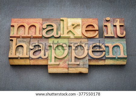 make it happen - inspirational phrase in letterpress wood type printing blocks stained by color inks against slate stone - stock photo