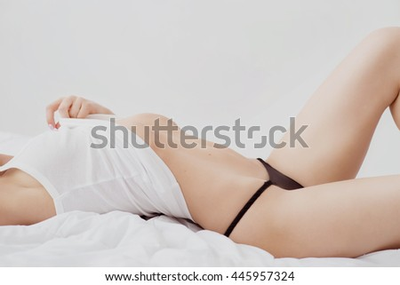 Make me naked. Sexually attractive slim woman lying in bed and undressing while seducing you - stock photo