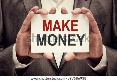 Make Money. Man holding a card with a message text written on it.  - stock photo