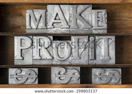 make profit phrase with dollar sign made from metallic letterpress type on wooden tray