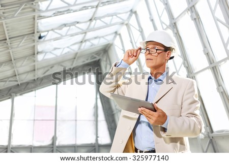 Make the progress. Professional agreeable architect keeping his glasses and holding laptop while looking up - stock photo
