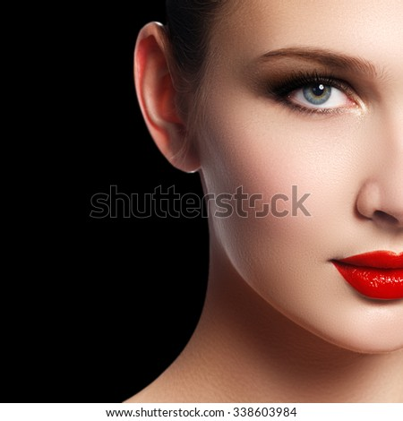 Make-up and cosmetics. Beauty woman face isolated on black background. Beautiful model girl makeup. Gorgeous lady with blue eyes and brown hair. Perfect skin. Professional make up. Red lips - stock photo