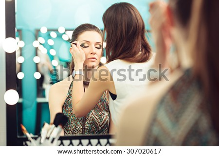 Make-up artist and model at work in front of mirror, selective focus on model's reflection
