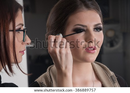 Make-up artist applying bright base color eyeshadow on model's eye and holding a shell with eyeshadow on background