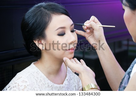 Make-up artist applying cosmetics on a beautiful young asian lady - stock photo