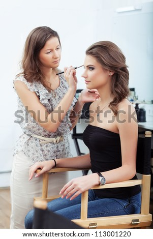 Make-up artist applying eyebrow make-up, selective focus on model - stock photo