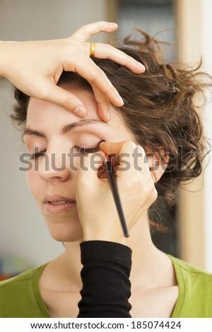 Make up artist applying  eyeshadow on beautiful female face - stock photo