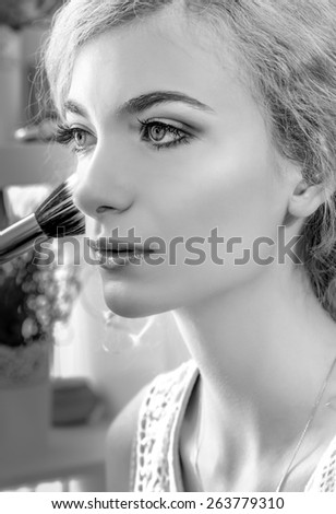 Make-up artist applying foundation powder or blush with makeup brush on model's cheeck, close up. Black and white - stock photo