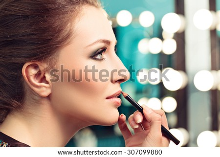 Make-up artist applying lip liner on model's lips, focus on model's eye - stock photo