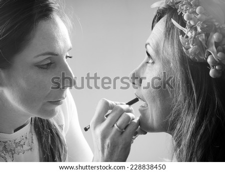make up artist applying lips line to the model with a pencil in black and white - stock photo