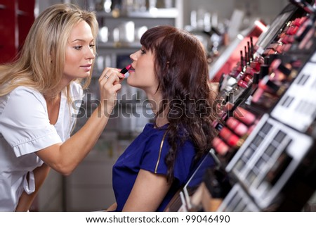 Make up artist applying lipstick to a customer in a beauty store. Selective focus. - stock photo