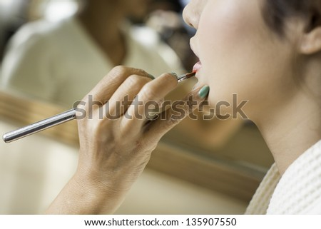 Make-up artist applying lipstick with a brush on woman's lip - stock photo
