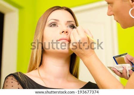Make up artist applying make up on a young and beautiful female model - stock photo