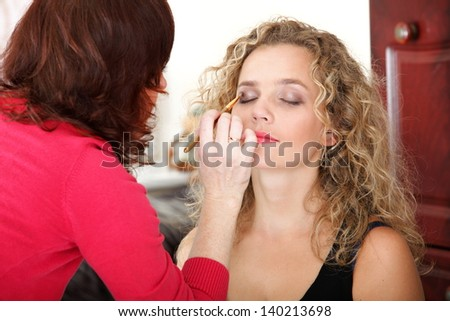 Make up artist applying make up to a fashion model indoor - stock photo