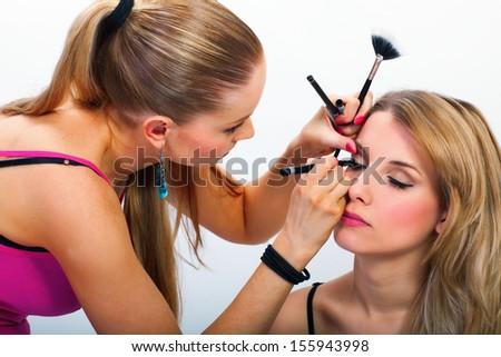 Make-up artist applying mascara on model's eyelashes - stock photo