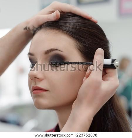 Make-up artist applying mascara on model's eyelashes, close-up, selective focus - stock photo