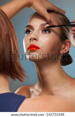 Make up artist at work, correcting eye lashes preparing motel to beauty photo session - stock photo