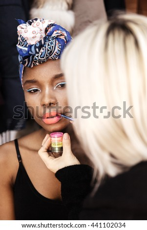 Make-up artist doing make up for young beautiful african american model - stock photo
