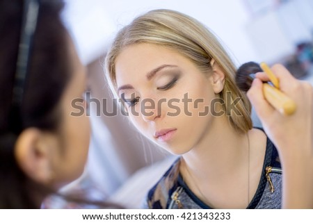make-up artist doing professional make up of young charming woman