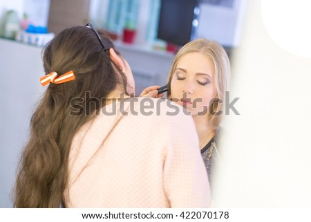 make-up artist doing professional make up of young charming woman - stock photo
