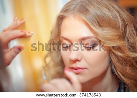 make up artist doing professional make up of young woman