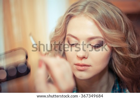 make-up artist doing professional make up of young woman. make-up artist doing make-up for the bride - stock photo
