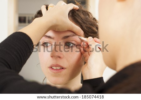 Make up artist hand and her model, real spontaneous image, pulling model eyebrows for better look - stock photo