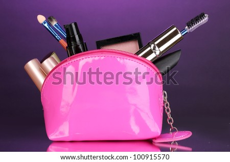 Make up bag with cosmetics and brushes on violet background - stock photo