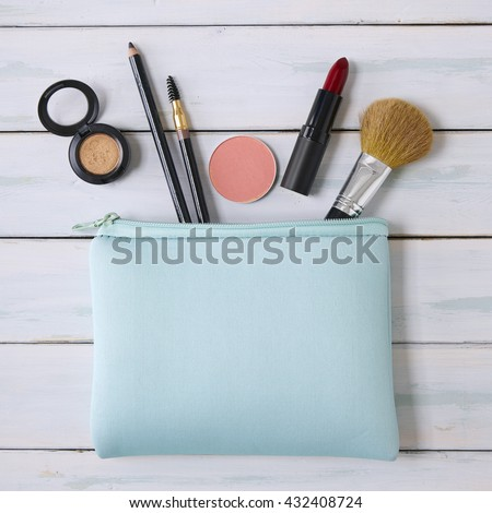 Make-up bag with products spilling out on a wooden background - stock photo