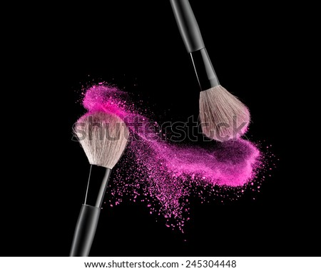 Make-up brush with pink powder explosion on black background - stock photo