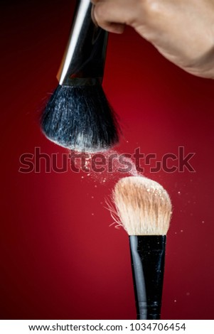 Make-up brush with white powder explosion on red background.
