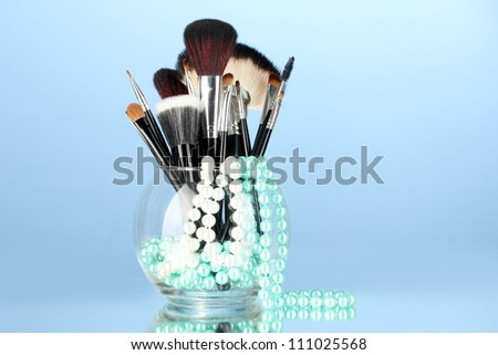 Make-up brushes in a bowl with pearl necklace on blue background - stock photo