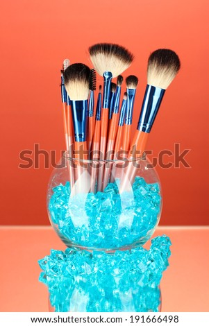 Make-up brushes in a bowl with stones on red background - stock photo