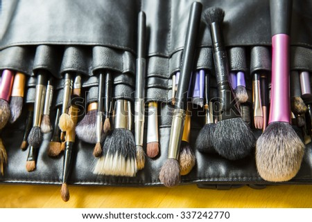 Make-up brushes in dark case - stock photo