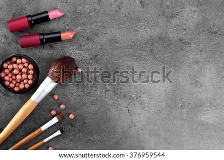 Make-up brushes, lipsticks, and blusher, on grey background - stock photo