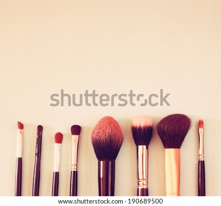 make up brushes set over wooden board. top view retro filtered. - stock photo