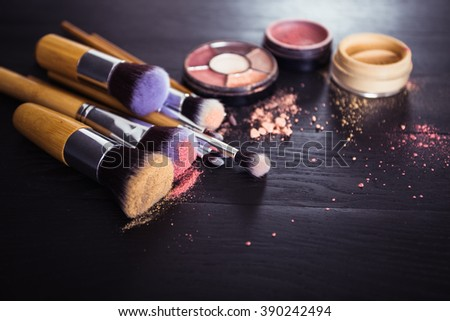 make up brushes with powder and rouge on a black wooden background - stock photo