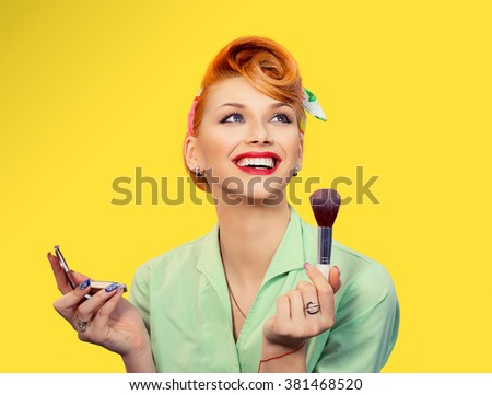 Make up. Close up portrait  headshot of Pinup retro style young woman pretty smiling girl teenager applying foundation powder, blusher with brush in green shirt holding mirror looking at you, camera - stock photo