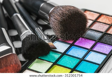 Make-up colorful eyeshadow palettes with makeup brushes. Focus in the middle frame. Shallow depth of field - stock photo