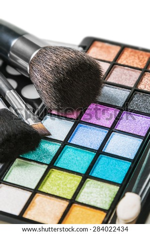 Make-up colorful eyeshadow palettes with makeup brushes. Focus in the middle of the frame on the blue shadows. Shallow depth of field - stock photo