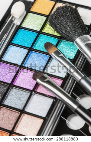 Make-up colorful eyeshadow palettes with makeup brushes. Focus in the middle of the frame on the green shadows. Shallow depth of field - stock photo