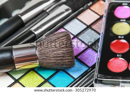 Make-up colorful eyeshadow palettes with makeup brushes. Focus on the bottom of the frame. Shallow depth of field - stock photo