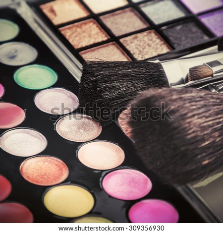 Make-up colorful eyeshadow palettes with makeup brushes. Focus on the brush in the middle of the frame. toned image - stock photo