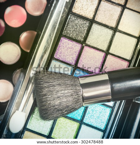 Make-up colorful eyeshadow palettes with makeup brushes. Focus on the brush. Shallow depth of field. toned image - stock photo