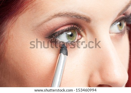 Make-up concept. Close-up image of green eyes woman applying makeup with pencil / brush.