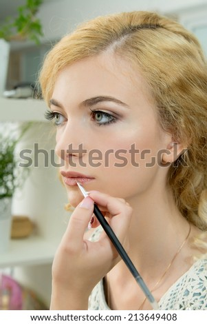 Make up. Cosmetic.Make-up artist applying lipstick on model's lips, close up. Applying Make-up.  - stock photo