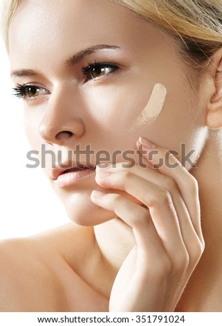 Make-up & cosmetics. Closeup portrait of beautiful woman model face with skin foundation on white background